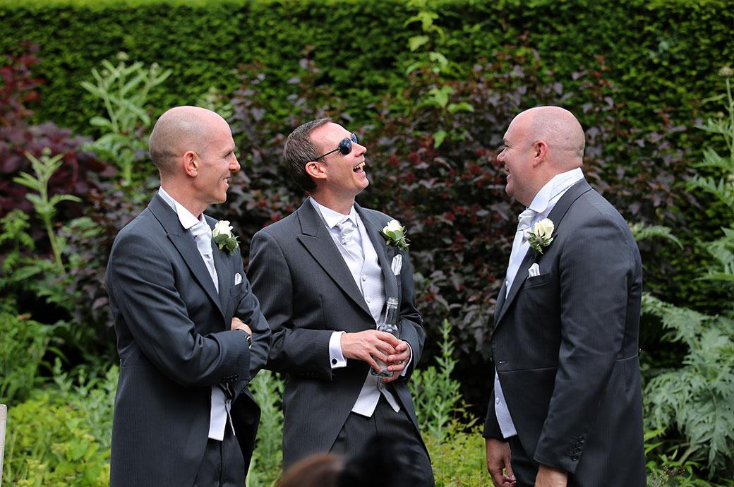 Groomsmen captured in this wedding picture  at a wedding reception at Great Fosters in Egham Surrey have a laugh over drinks on the terrace
