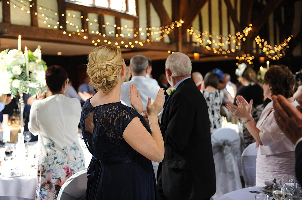 A wedding picture of guests standing and applauding in the atmospheric Tithe Barn at  Great Fosters Surrey lit with fairy lights as the newlywed couple arrive for the wedding breakfast