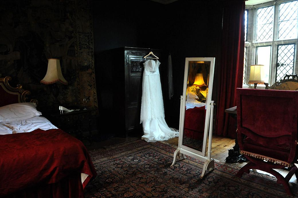 Beautiful wedding dress hanging from an old oak wardrobe in the dark and richly attired Tapestry Room at the Grade One Listed Great Fosters Hotel in Egham Surrey