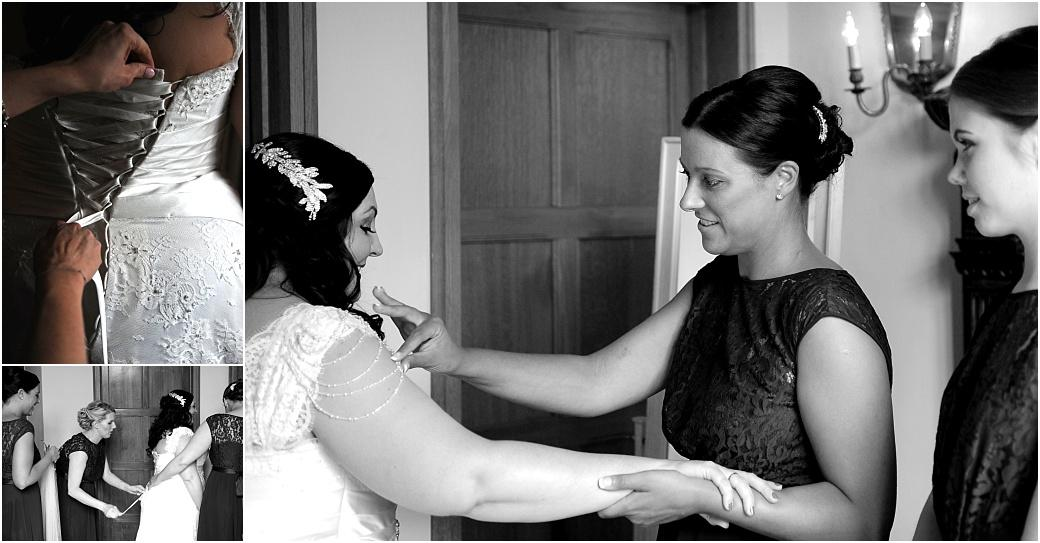 Bridesmaids helping the Bride with her wedding dress captured in the rich and stately Tapestry Room at Great Fosters in Egham an outstanding Surrey wedding venue