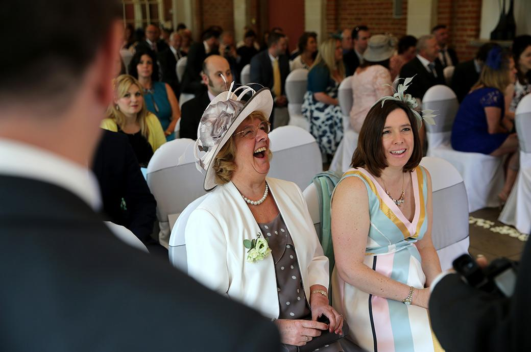 Wedding photograph taken in the marriage ceremony room in The Orangery at Surrey wedding venue Great Fosters of the mother of the Groom laughing at a comment from her son