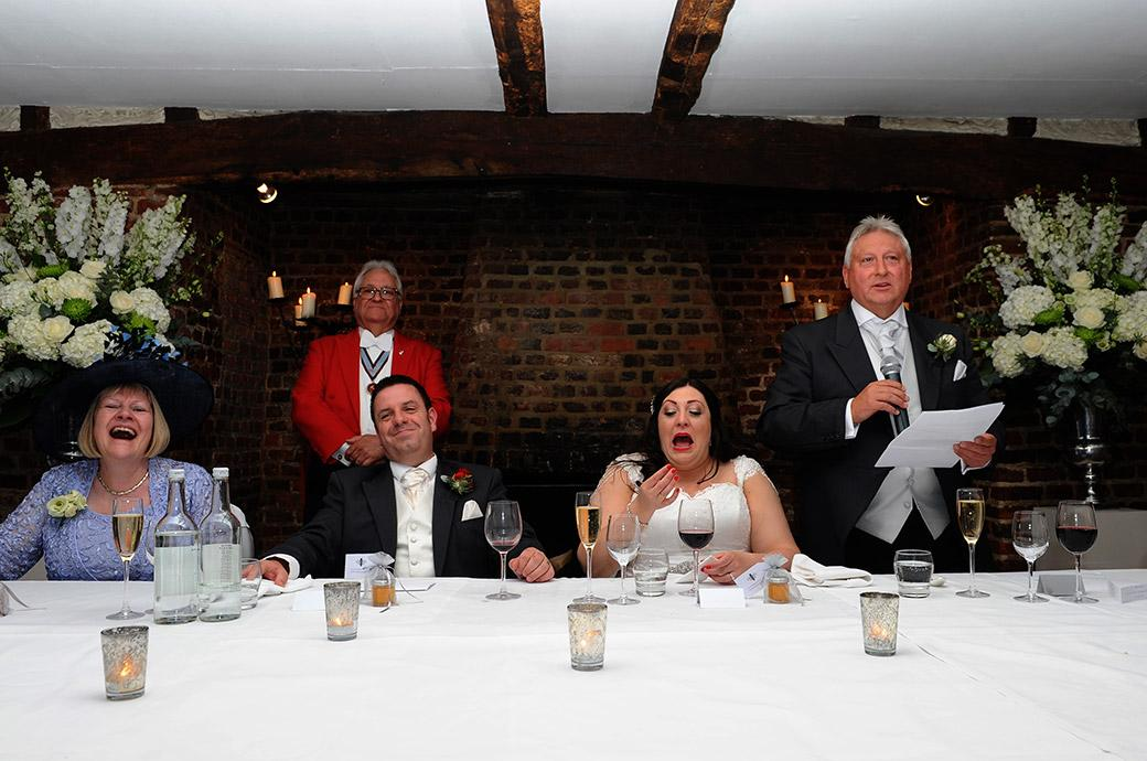 Father of the Bride causes much mirth and laughter on the top table during an entertaining speech held in the ancient Tithe Barn in Great Fosters a Surrey wedding venue in Egham