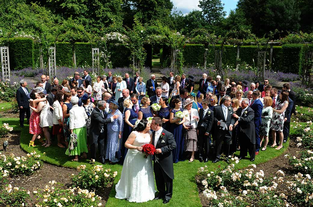 Funny wedding picture taken in the sunken circular rose garden at Surrey wedding venue Great Fosters in Egham for everyone to copy the bride and groom and kiss