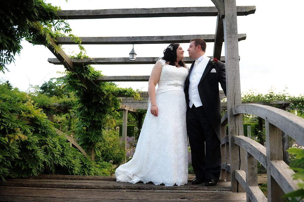 All smiles and happiness at a  Great Fosters Surrey wedding in Egham as a newlywed couple look into each others eyes as they stand on the charming wooden Japanese Bridge