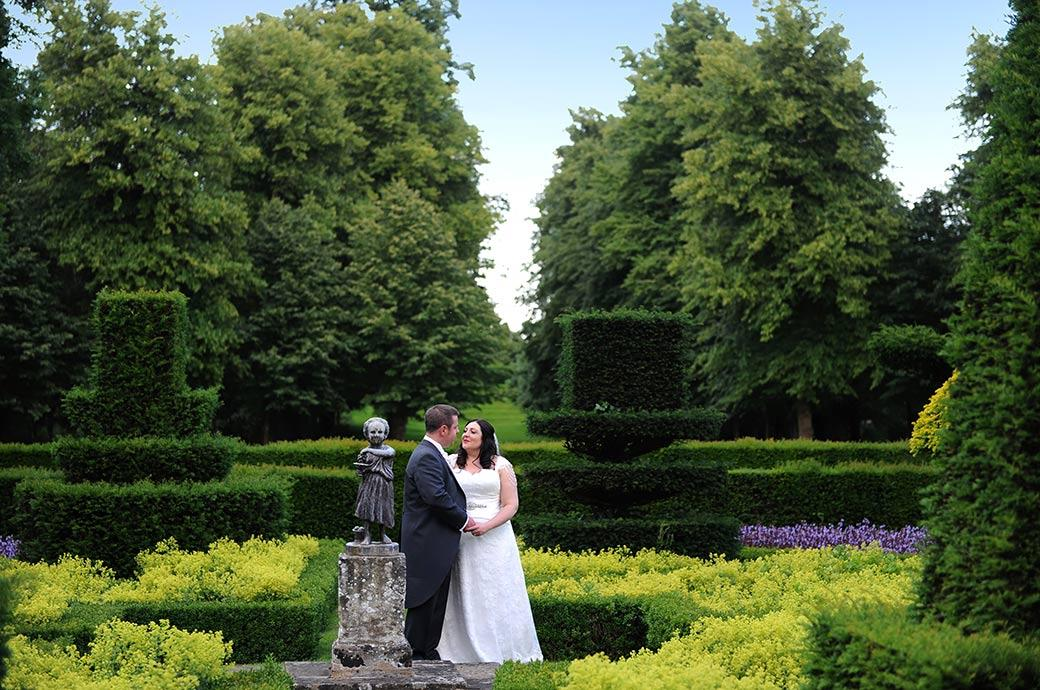 Classic romantic wedding photograph of the Bride and groom at Great Fosters Surrey standing together holding hands in the beautiful parterre gardens next a statue