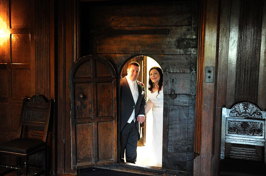 A smiling Bride and Groom captured in this wedding photo at the wonderful Surrey wedding venue Great Fosters as they peer through the wicket  of the stout oak front door