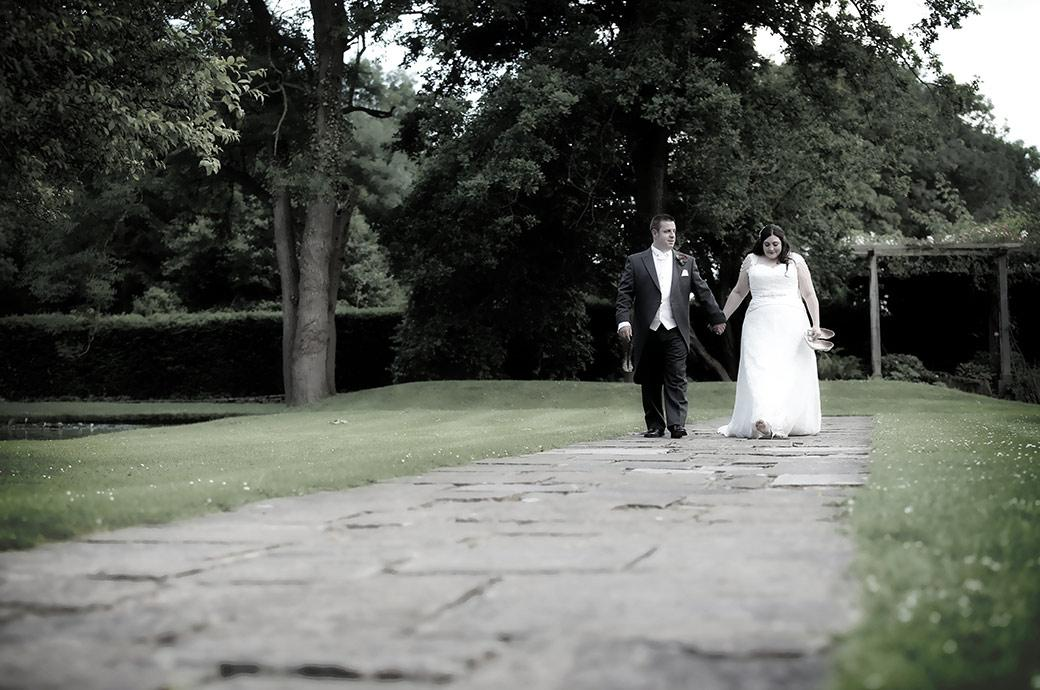 Hand in the hand the newlyweds take time to reflect on the day as they walk along flagstones through the beautiful grounds of the magnificent Surrey venue Great Fosters in Egham