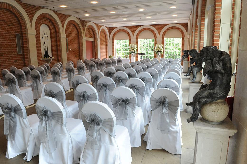 The light elegant and airy Orangery at the magnificent Surrey wedding venue Great Fosters in Egham dressed for the wedding ceremony and awaiting the arrival of the guests