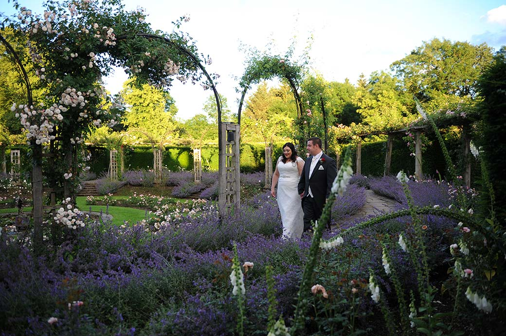 Lovers talk as they walk hand in hand during a romantic walk through the beautiful grounds including the beautiful sunken rose garden after their wedding at Great Fosters Surrey