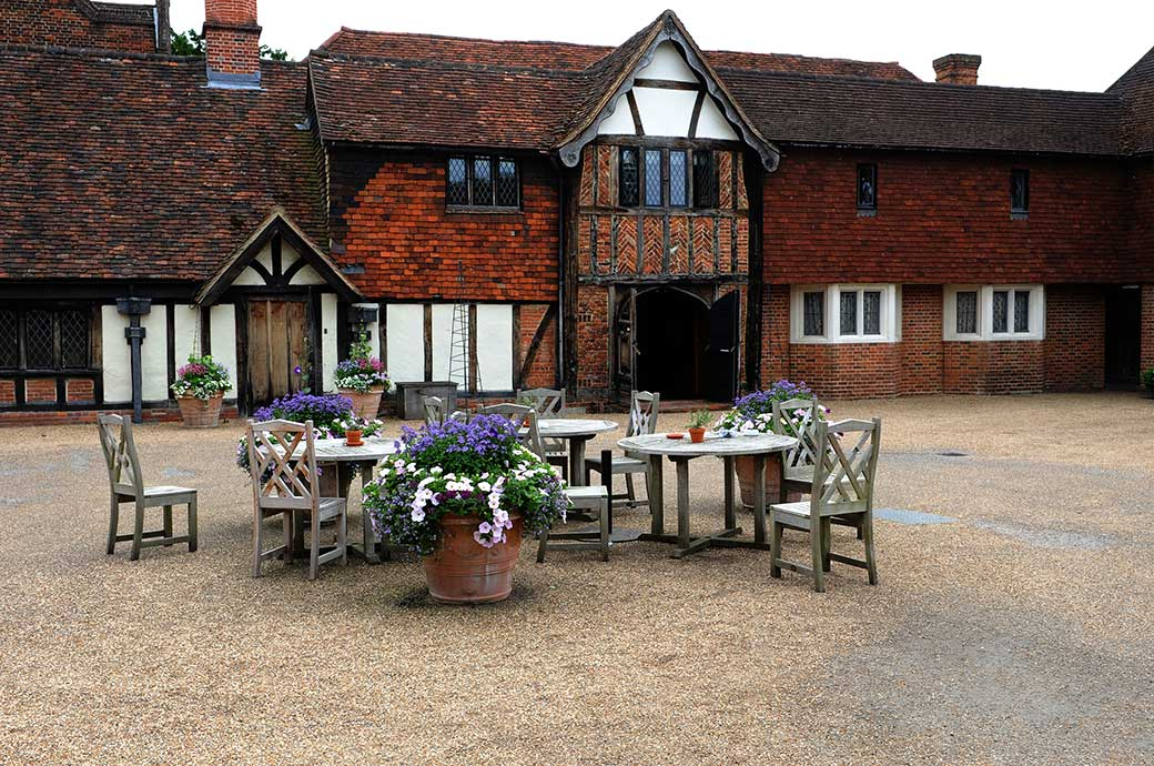 Wooden tables with pots of flowers await arriving guests in the rustic courtyard outside the entrance to the Tithe Barn at Surrey wedding venue Great Fosters Hotel in Egham