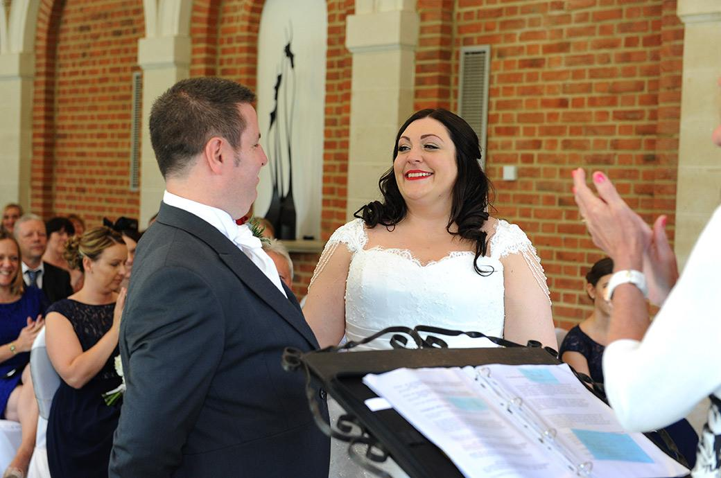 Smiles happiness and applause during the marriage ceremony in The Orangery at Surrey wedding venue Great Fosters as the Bride and groom are announced husband and wife