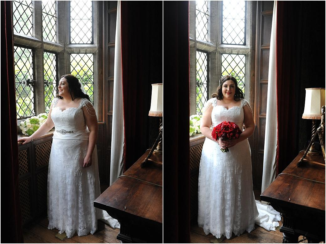 A smiling Bride at Great Fosters wedding venue Egham Surrey standing by the window in The Tapestry Room admiring the view and holding her wedding bouquet