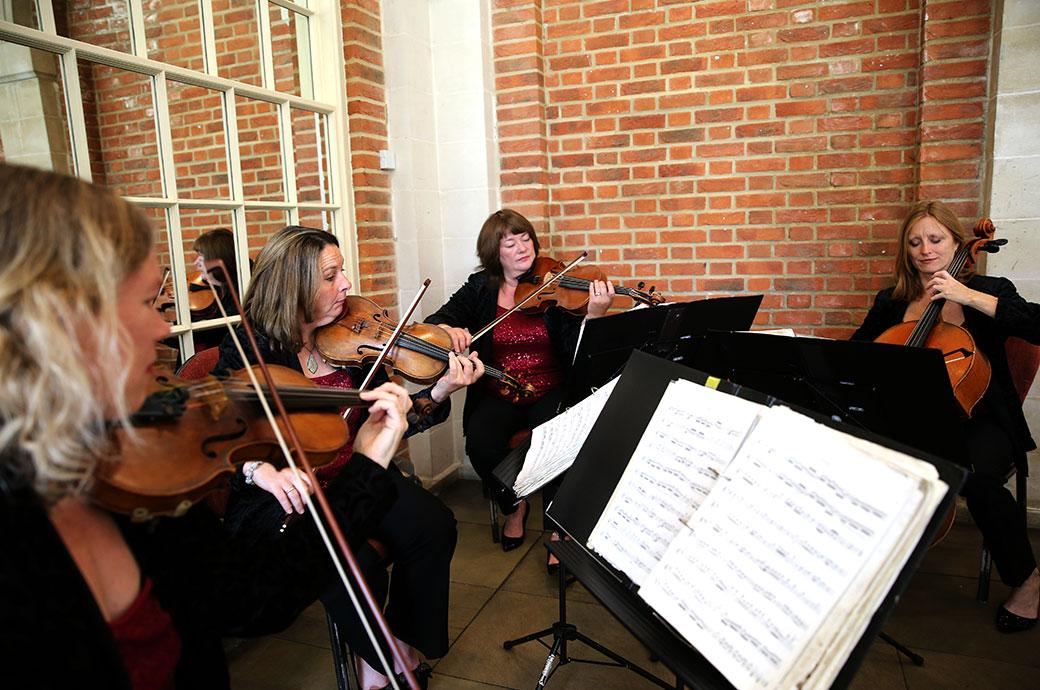 Wedding photograph of a string quartet setting the tone of the morning with some beautiful melodic background music at Surrey wedding venue Great Fosters in The Orangery