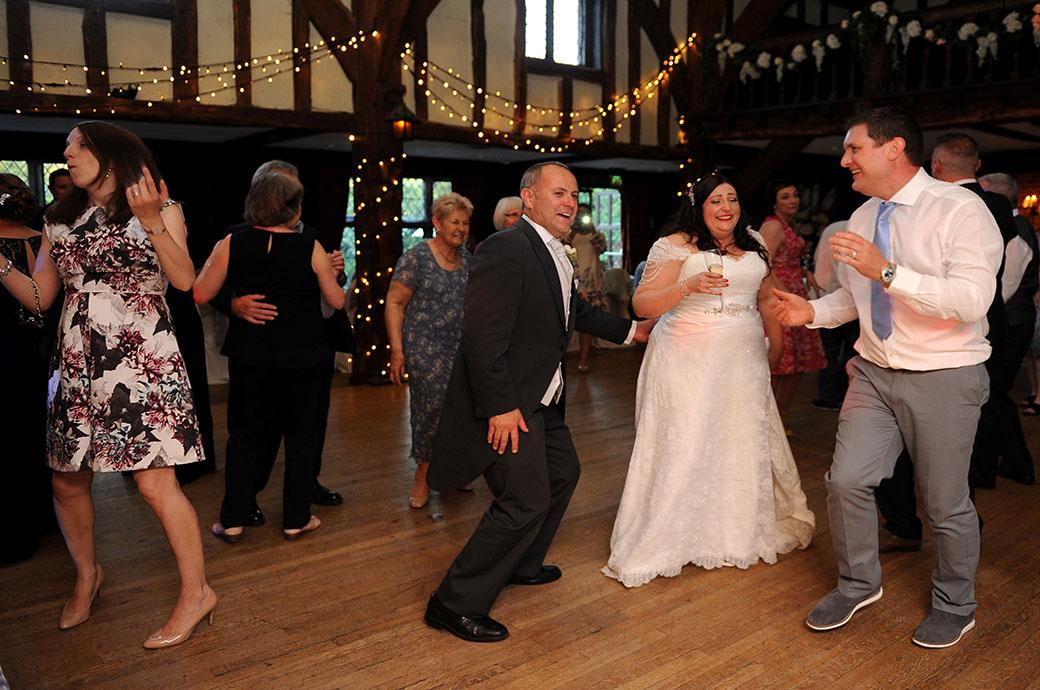 Bride with champagne in hand captured at the wonderful Surrey wedding venue Great Fosters enjoying herself on the dance floor of the atmospheric Tithe Barn