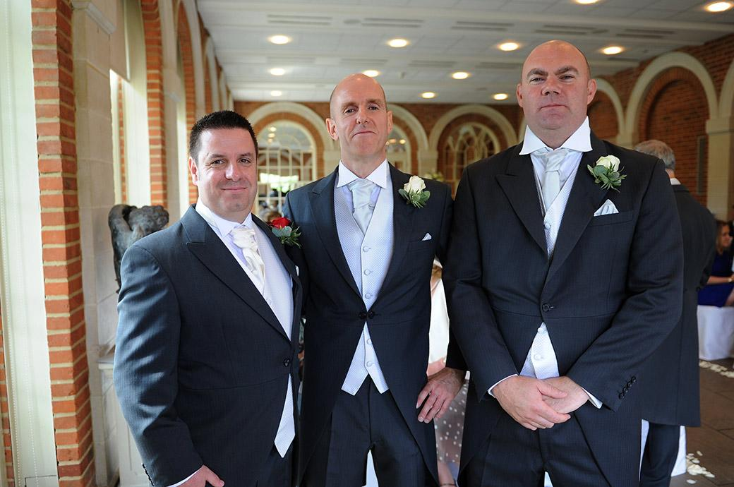 A smiling Groom stands with his best men as they await the arrival of the Bride at the wonderful Great Fosters wedding venue in Egham Surrey in The Orangery