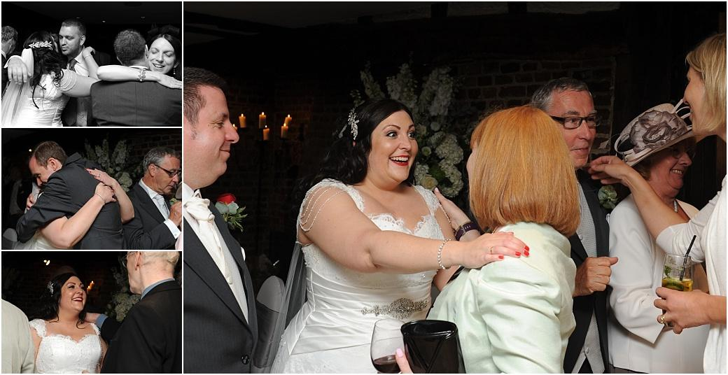 Smiles hugs and kisses for the Bride and groom and their family at Surrey wedding venue Great Fosters as they greet guests in a receiving line in the ancient Tithe Barn