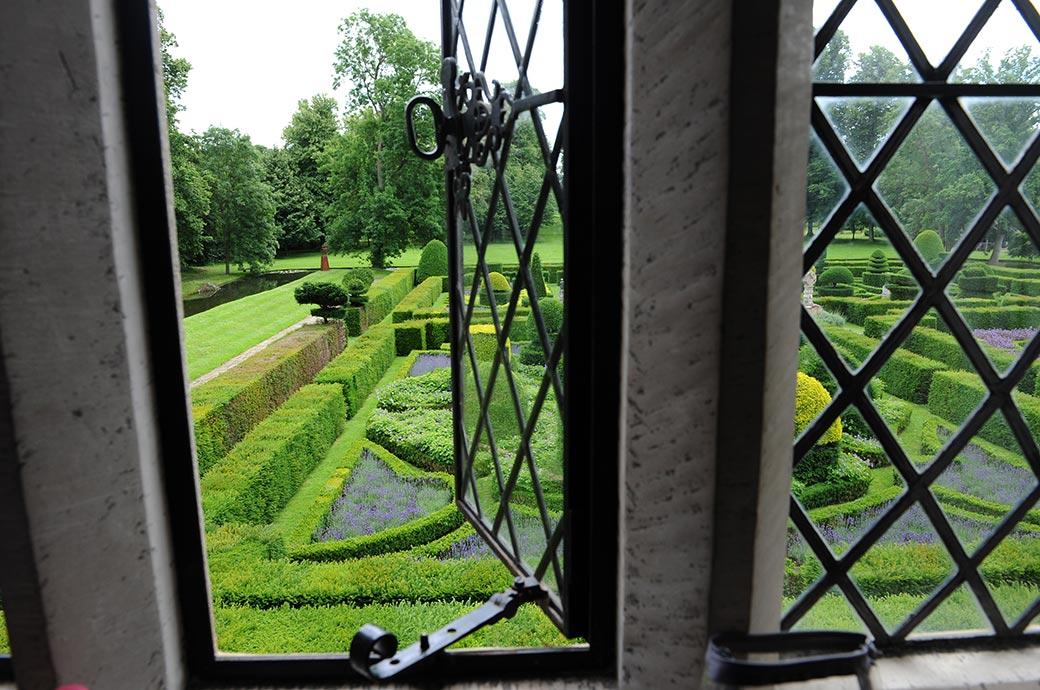 The luscious green and ornate formal gardens at Surrey wedding venue Great Fosters Hotel in Egham as seen by the Bride whilst getting ready in the grand Tapestry Room
