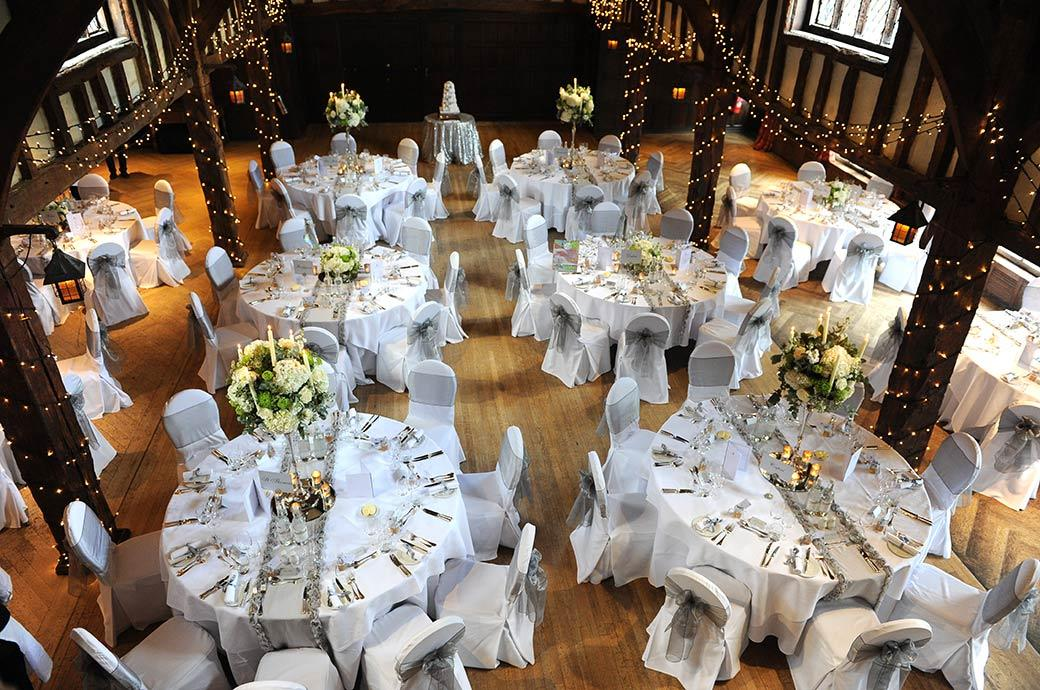 Wedding photograph of the atmospheric wedding breakfast table settings with fairy lights in the Tithe Barn at  Surrey wedding venue Great Fosters  as seen from the minstrel gallery