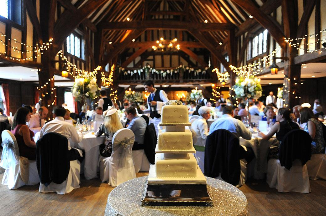 Atmospheric wedding photograph of a wedding breakfast at Great Fosters in Egham Surrey  in full swing taken from behind the wedding cake in the ancient Tithe Barn