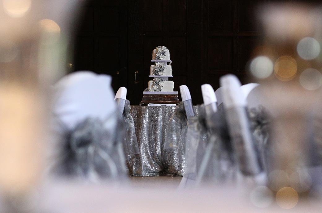 Evocative view of the wedding cake located at the end of the Tithe Barn past the silver dressed chair backs at a Great Fosters Egham wedding breakfast in Egham Surrey