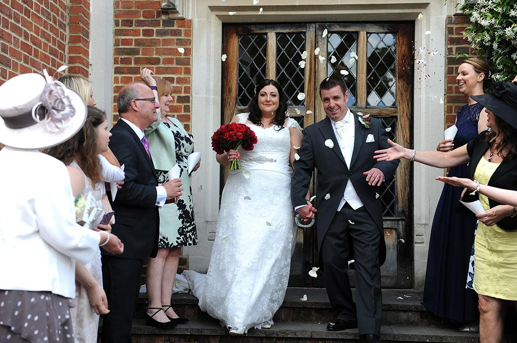 Bride and groom looking ahead as they descend the steps from the Painted Hall into a line of confetti throwers at Surrey wedding Great Fosters out on the terrace