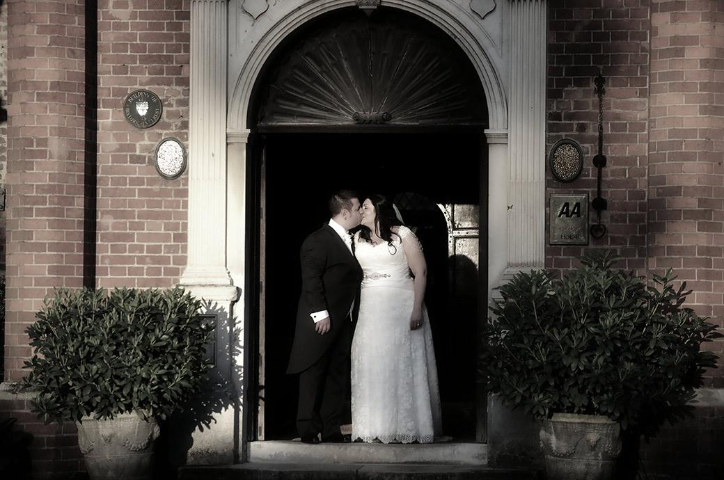 Wedding picture of a Bride and groom captured romantically kissing outside the grand main door in the dying sun at Great Fosters in Egham Surrey