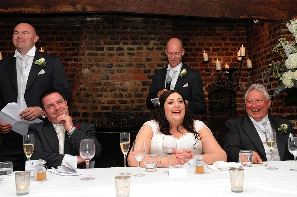 Laughter and grimaces captured at the top table in the Tithe Barn at Surrey wedding venue Great Fosters during the best men's wedding speech with their comments about the groom