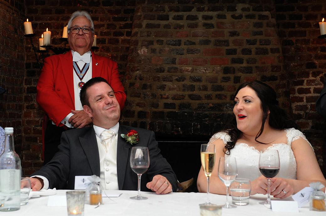 Wry smiles from the Bride and Groom at Great Fosters Tithe Barn in Egham Surrey as they listen to the funny and quite possibly far fetched wedding speech from the best men