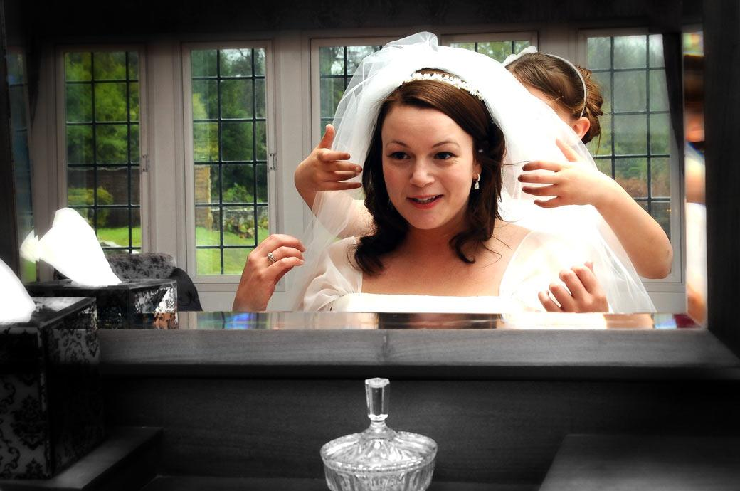 A lovely Bride having her veil adjusted in the mirror wedding picture taken at Greyfriars House nr Guildford by Surrey Lane wedding photography