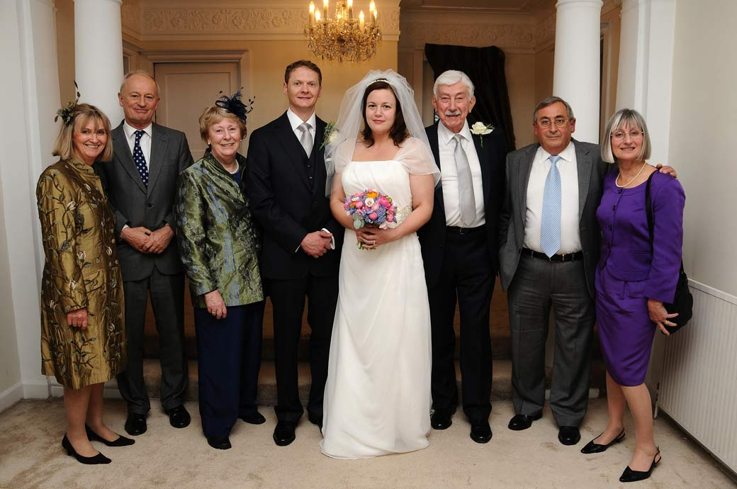 A pleasant close family group wedding photograph taken inside Greyfriars House a Surrey wedding venue nr Guildford by Surrey Lane wedding photography