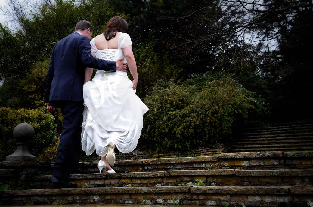 A gentle romantic moment captured in this wedding photo as the Groom gently holds his wife as they walk up the steps at Greyfriars House nr Guildford