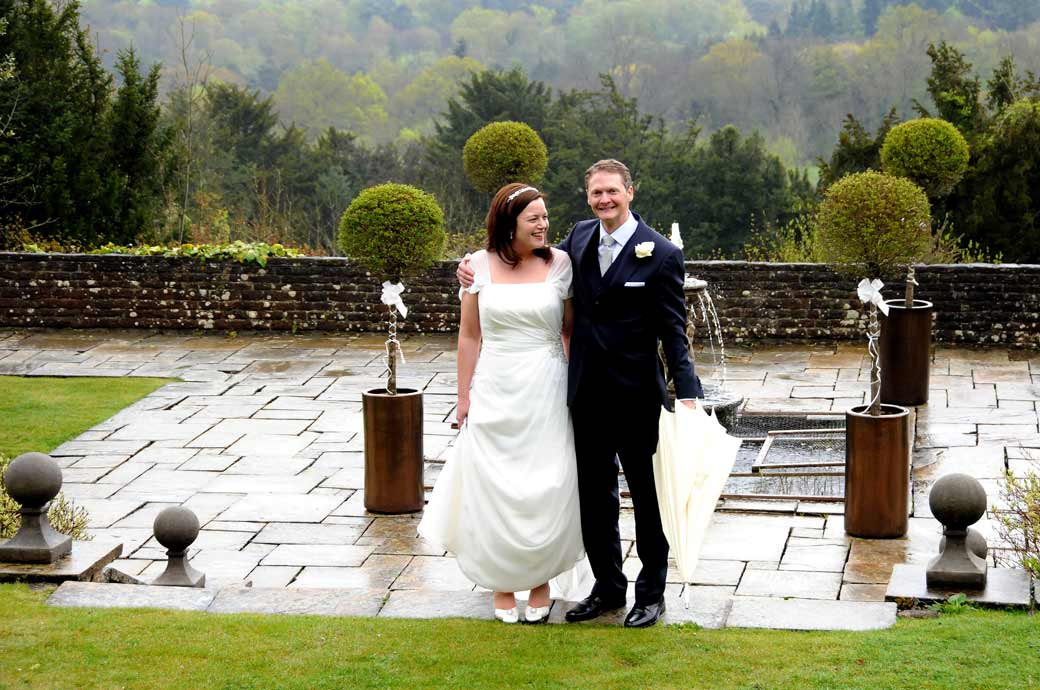 A happy wedding couple photo smiling together in the garden with the beautiful misty Surrey Hills in the background nr Guildford at Greyfriars House