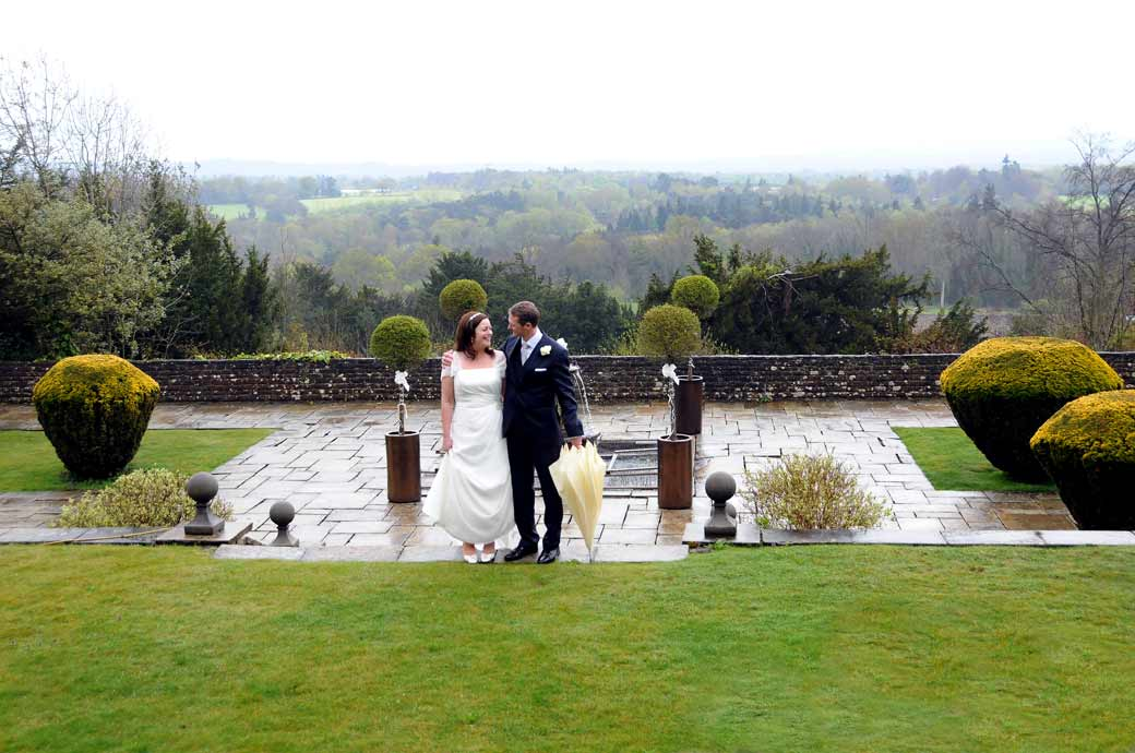 Groom with his happy Bride in the garden with stunning views of the Surrey Hills taken at the Surrey wedding venue Greyfriars House nr Guildford