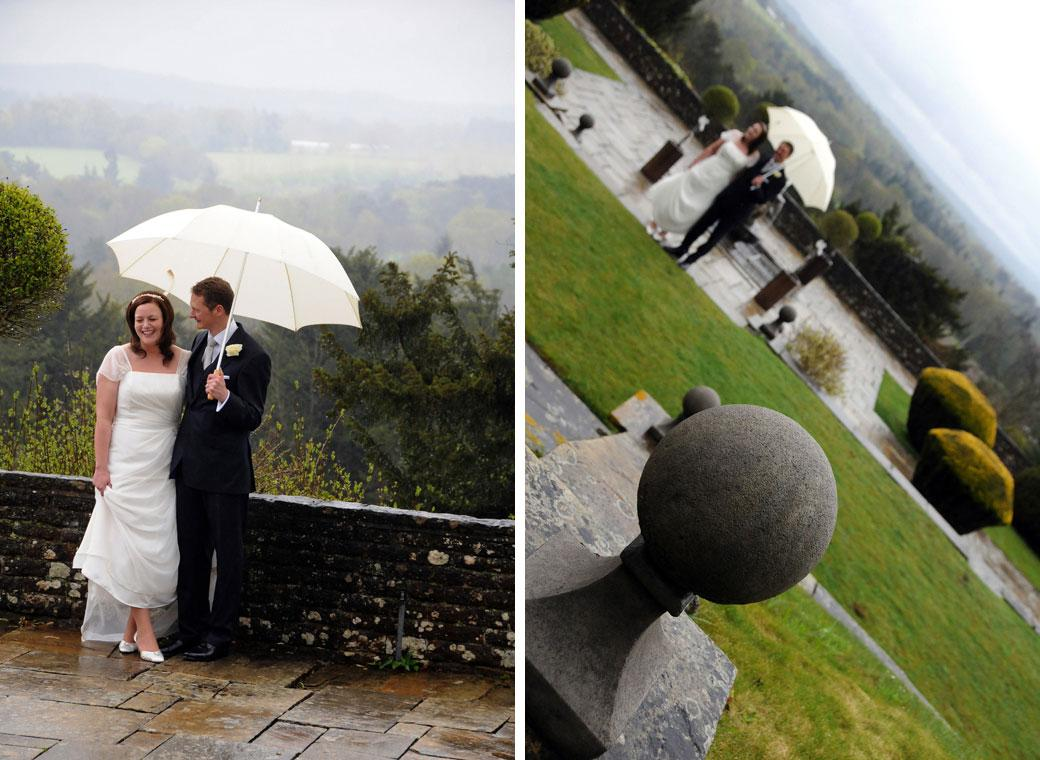 Two fresh wedding pictures of newly-weds under a white umbrella with views of the misty Surrey Hills in the background nr Guildford at Greyfriars House