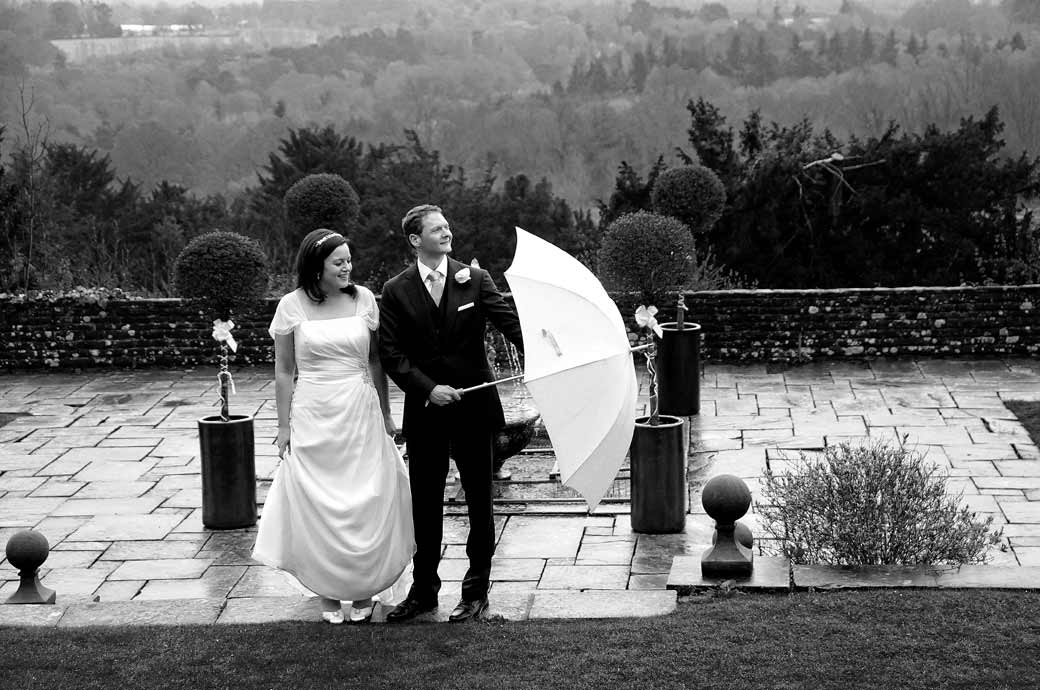 'A time for the umbrella' wedding photograph moment taken by Surrey Lane wedding photography in the garden at Surrey wedding venue Greyfriars House