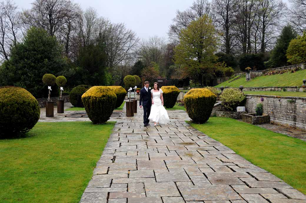 Newly-weds walking and chatting along the wet flagstones wedding picture  taken in the garden at Greyfriars House a Surrey wedding venue nr Guildford