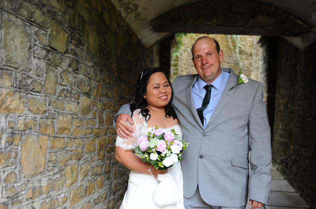 Happiness and contentment for a proud Groom in this wedding picture taken at the popular Surrey tourist spot Guildford Castle Gardens with his arm around his smiling Bride