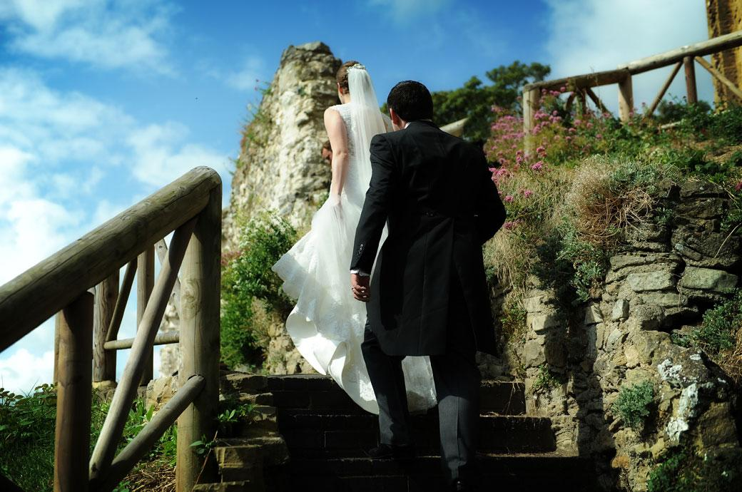 Wedding photo of a Bride and Groom walking up the steep stone steps towards the keep in Guildford Castle Gardens captured by a Surrey Lane wedding photographer