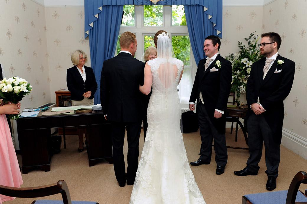 Bride and a smiling Groom stand before the registrar in this wedding photograph taken in the Guildown Room at the ever popular Surrey wedding venue Guildford Register Office