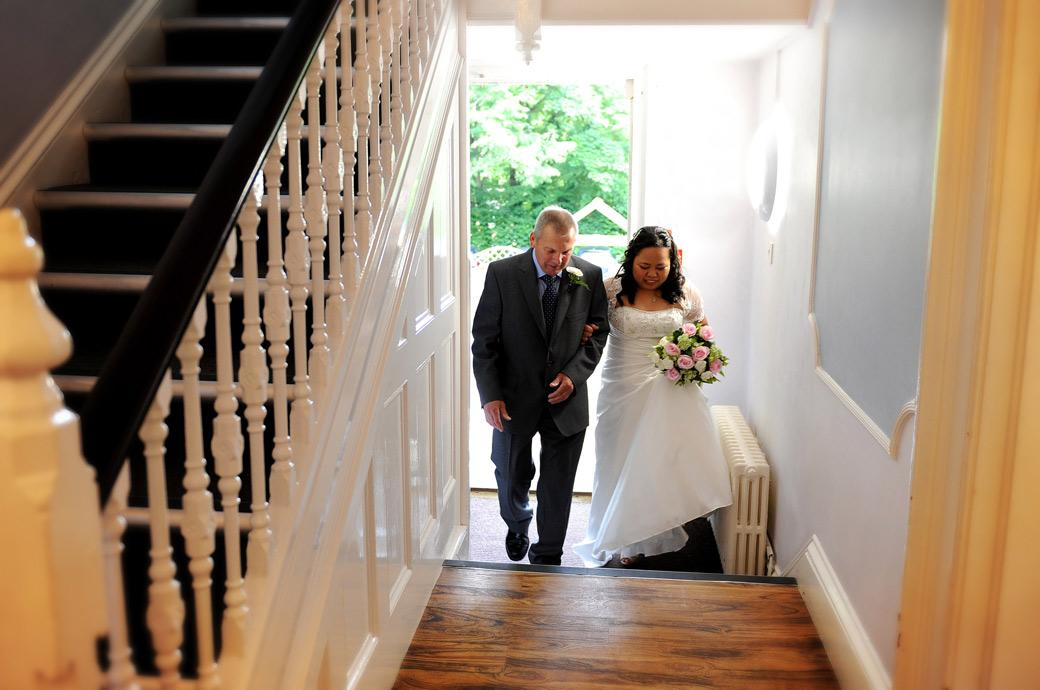 Bride in a wedding photo walking in through the main front door  of Artington House Guildford Register Office in Surrey on the arm of her father in law
