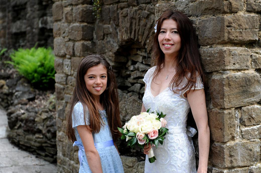 Smiling Bride and daughter bridesmaid pose for the Surrey Lane wedding photographer in the beautiful Guildford Castle Gardens by a stone entrance wall