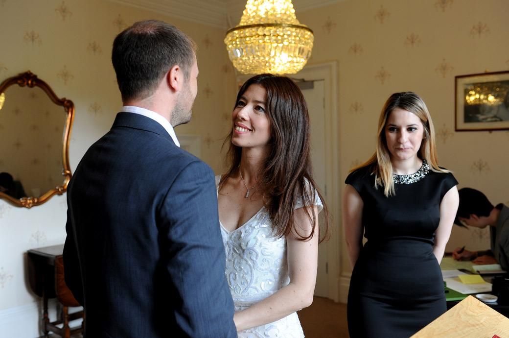 Bride at Surrey wedding venue in Guildford Register Office Artington House looks lovingly at her Groom in this touching and  romantic wedding picture