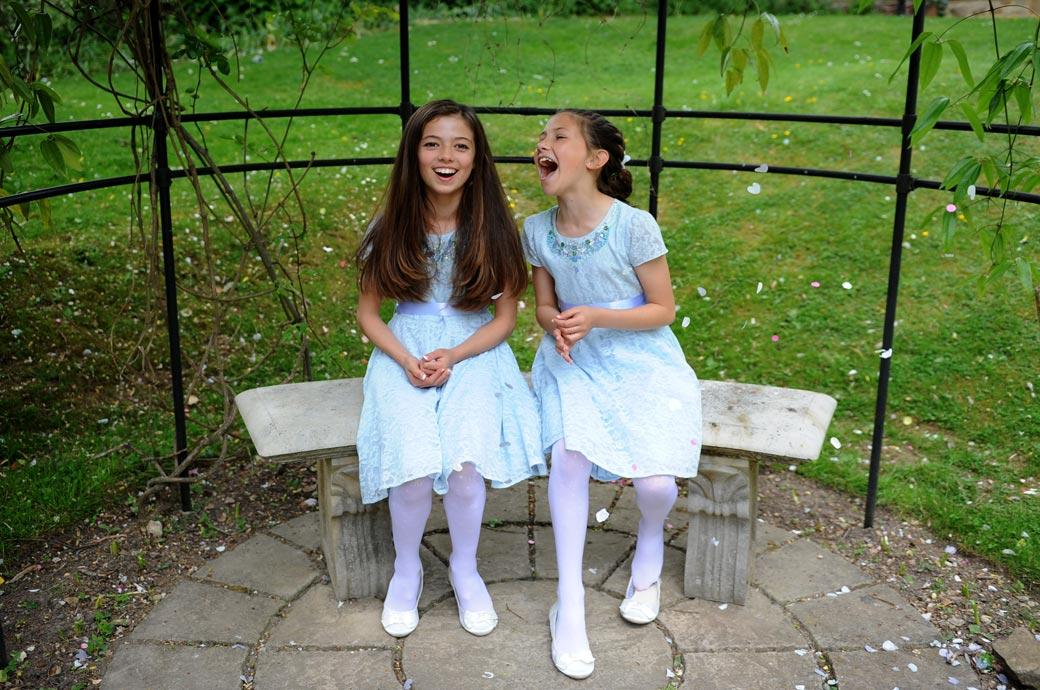 Cute little bridesmaids sitting on the stone bench outside Surrey wedding venue Guildford Register Office playing around and enjoying themselves