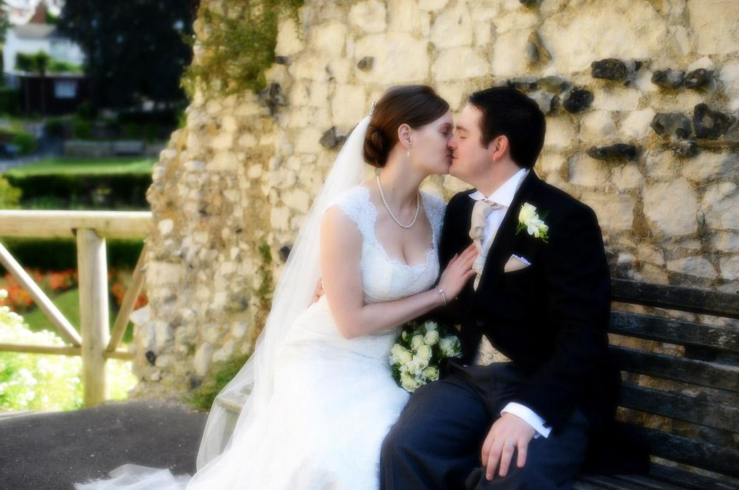 A close up soft focus wedding photograph of the beautiful Bride kissing her husband as they sit on a bench in the ancient and pretty Guildford Castle Gardens in Surrey