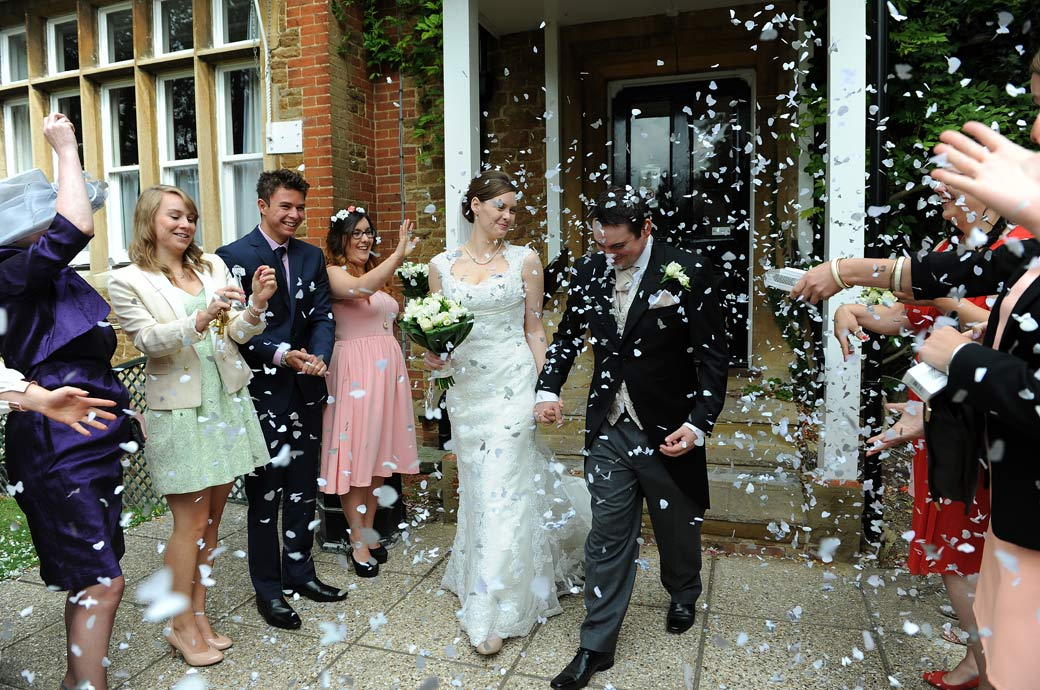 Fun confetti throwing time captured in this wedding photo taken by Surrey Lane wedding photographers out on the Guildford Register Office terrace