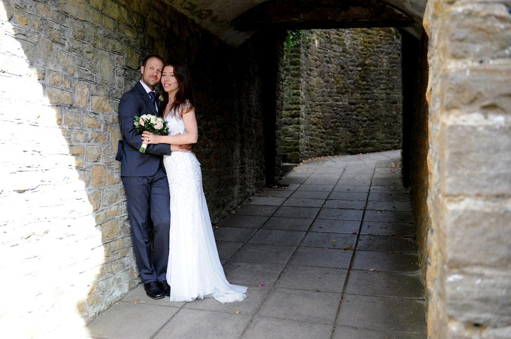 Content Bride and Groom with their heads together as they look out from the covered alleyway in Guildford Castle Gardens Surrey after their marriage an hour earlier