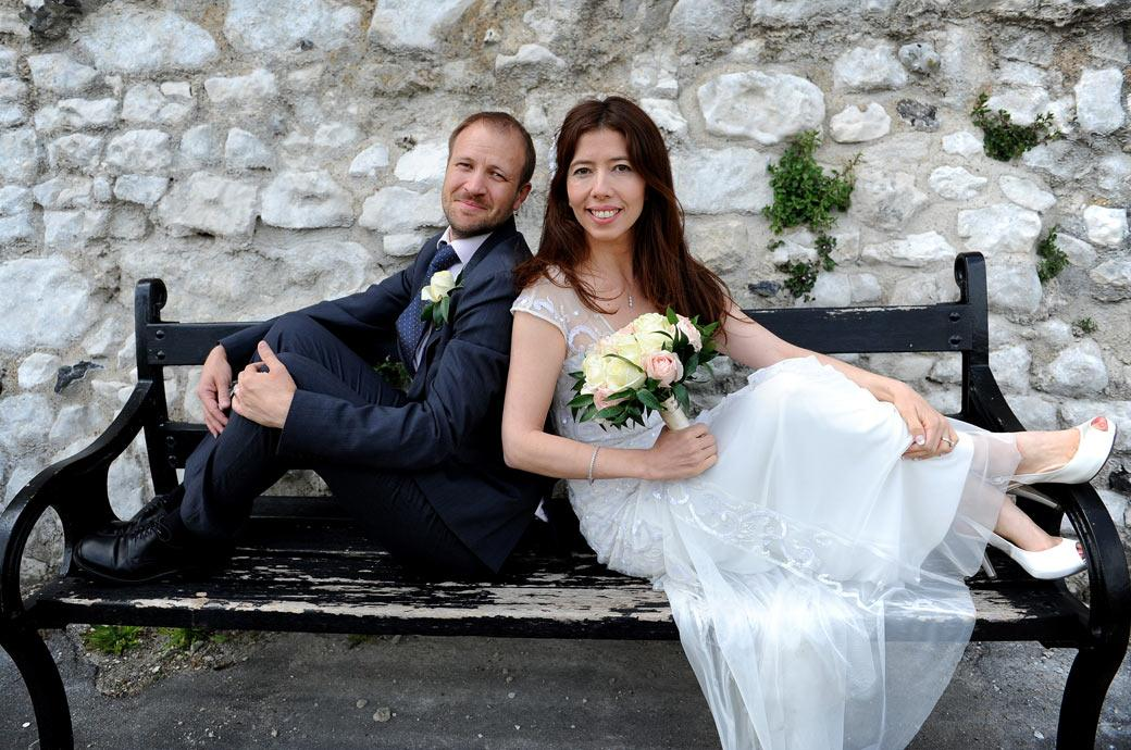 Wedding photograph of the smiling newlyweds having fun on a park bench in Guildford Castle Gardens after their marriage at Guilford Register Office earlier
