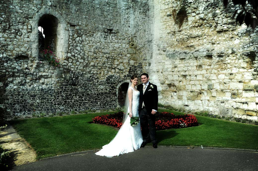 A proud Bride stands with her smiling Groom in front of the dramatic Guildford Castle walls captured in this wedding photograph by Surrey Lane wedding photographers