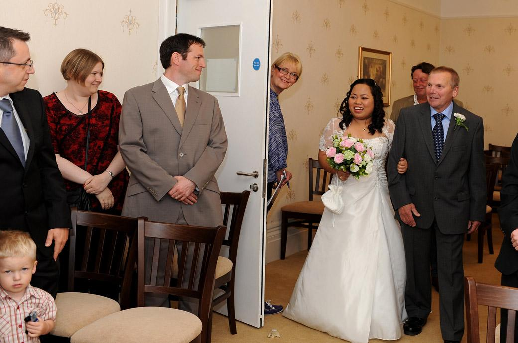The Bride on her father in laws arm captured in Surrey at Guildford Register Office Artington House walking down the aisle past the smiling guests in the Guildown Room