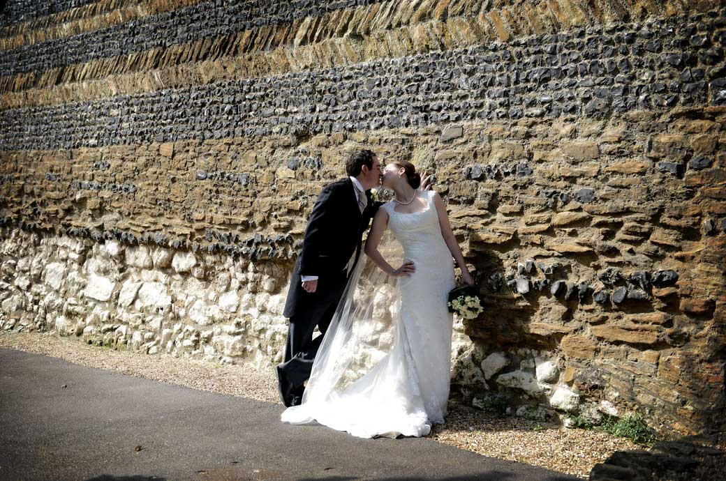 A dramatic snatched kiss captured in this wedding photograph taken before the the multi layered stone wall of the castle in Guildford Castle Gardens in Surrey